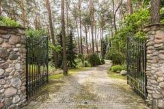 Bügeln Sie das Eingangstor und steinige Straße, die im Wald zu das Haus führen lizenzfreie stockfotografie