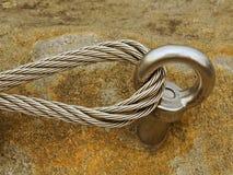 Bügeln Sie das verdrehte Seil, das im Block durch Schrauben snaphooks geregelt wird Detail des Endes des verankerten Seils Stockbilder
