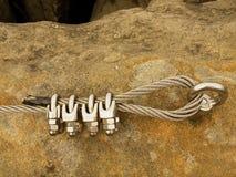 Bügeln Sie das verdrehte Seil, das im Block durch Schrauben snaphooks geregelt wird Detail des Endes des verankerten Seils Lizenzfreies Stockfoto