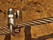 Bügeln Sie das verdrehte Seil, das im Block durch Schraubenkarabinerhaken geregelt wird Detail von Tampen verankert in Felsen Lizenzfreie Stockfotos