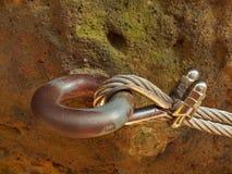 Bügeln Sie das verdrehte Seil, das im Block durch Schraubenkarabinerhaken geregelt wird Detail von Tampen verankert in Felsen Stockfoto