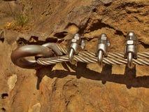 Bügeln Sie das verdrehte Seil, das im Block durch Schraubenkarabinerhaken geregelt wird Detail von Tampen verankert in Felsen Stockfotos