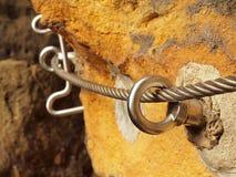 Bügeln Sie das verdrehte Seil, das im Block durch Schraubenkarabinerhaken geregelt wird Detail von Tampen verankert in Felsen Lizenzfreie Stockbilder