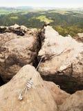 Bügeln Sie das verdrehte Seil, das zwischen Felsen im Bergsteigerflecken über ferrata ausgedehnt wird Seil geregelt im Felsen Stockbilder