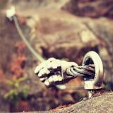 Bügeln Sie das verdrehte Seil, das zwischen Felsen im Bergsteigerflecken streched ist Seil geregelt im Block durch Schraubenkarab Stockbild