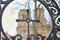 Bügeln Sie Kreuz mit einer Kirche im Hintergrund Stockfotografie