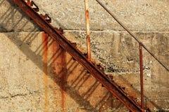 Bügeln Sie rostiges verlassenes Treppenhaus auf dem Hintergrund einer Betonmauer Lizenzfreies Stockfoto