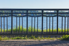 Bügeln Sie Zaun vor dem Fluss an einem sonnigen Tag Stockbilder