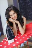 Bügelnde Dienstleistungen der glücklichen jungen hübschen Frau Lizenzfreie Stockfotografie
