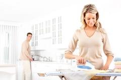 Bügelnde Kleidung der Frau Stockbilder