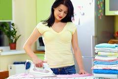 Bügelnde Kleidung der hübschen Frau zu Hause lizenzfreies stockfoto