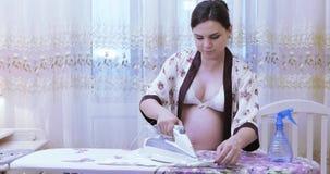 Bügelnde Kleidung des schwangeren Mädchens stock video footage