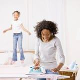 Bügelnde Wäscherei der Hausfrau, während Mädchen auf Bett springt Stockbilder