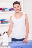 Bügelndes Hemd des Mannes bevor dem Gehen für Arbeit Stockfotos