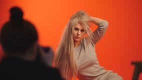 Bühne hinter dem Vorhang: blondes weibliches Modell, das für Fotografen im roten Studio aufwirft Stockfotos