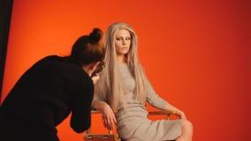 Bühne hinter dem Vorhang: blondes weibliches Modell, das für Fotografen im roten Studio aufwirft Stockbild
