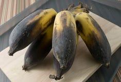 Bündel alte Bananen-Frucht auf einem hölzernen Brett Stockfoto