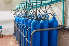 Bündel blaue Gasflaschen mit Manometern stockfotos