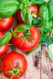 Bündel bunte organische Tomaten des neuen Seils mit Wassertropfen zerstreute auf den verwitterten hölzernen Tabellen-, Grünen und Lizenzfreie Stockfotografie