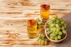 Bündel der frischen reifen grünen Trauben im Weidenkorb auf Stück Sackleinen und zwei Gläsern mit Traubensaft auf einem hölzernen Lizenzfreies Stockbild