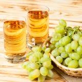 Bündel der frischen reifen grünen Trauben im Weidenkorb auf Stück Sackleinen und zwei Gläsern mit Traubensaft auf einem hölzernen Stockfotos