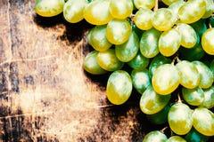 Bündel der frischen reifen weißen Trauben auf einer hölzernen strukturellen Oberfläche Lizenzfreie Stockfotos