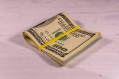 Bündel der hundert Dollarscheine mit Gummi auf hölzernem tabl Lizenzfreie Stockfotografie
