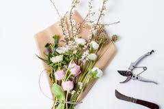 Bündel des Frühlinges blüht auf Packpapier mit Werkzeugen Lizenzfreie Stockfotografie