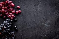 Bündel des Rotes und der blauen Traube auf schwarzem copyspace Draufsicht des Hintergrundes Stockfotografie