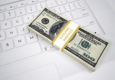 Bündel Dollarscheine, die auf Computertastatur liegen Stockbilder