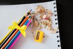 Bündel farbige Bleistifte schärfte mit einem gelben Bogen, einem Bleistiftspitzer und Schnitzeln Stockbild