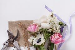 Bündel Frühlingsblumen mit Werkzeugen Stockbilder