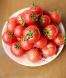 Bündel frische Tomaten mit Tropfen auf einer Platte Stockfotos