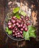 Bündel frische Trauben mit Grün verlässt im metallischen Korb auf rustikalem hölzernem Hintergrund Stockfotos
