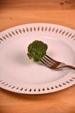 Bündel frischer grüner Brokkoli auf weißer Platte über hölzernem Hintergrund Lizenzfreies Stockfoto