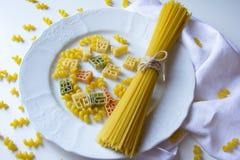 Bündel gebundene Spaghettis haftet an der weißen Platte mit buntem fusilli und an den simbolic Teigwaren am weißen Hintergrund stockbild