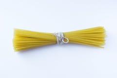 Bündel gebundene Spaghettis haftet am weißen Hintergrund Stockfoto
