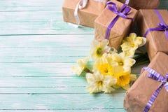Bündel gelbe Narzissenblumen und eingewickelte Geschenkboxen Lizenzfreies Stockfoto