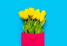 Bündel gelbe Tulpen in der kühlen Einkaufstasche auf dem wunderbaren Blauen lizenzfreies stockfoto