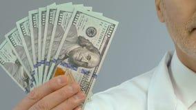 Bündel Geld in Doktorhand, teure Behandlung, zahlende Medizinnahaufnahme stock video