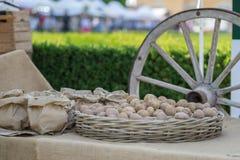 Bündel Kartoffeln im Abtropfbrett und großer hölzerner Kampfwagen s drehen herein Hintergrund Stockfoto