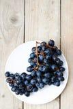 Bündel reife blaue Trauben auf einem hellen hölzernen Hintergrund Stockfoto
