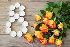 Bündel rosafarbene und kleine Kerzen der Orange in der Form Nr. 8, acht auf hölzernem Hintergrund Glücklicher internationaler Fra stockbilder