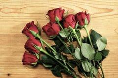 Bündel rote Rosen auf dem Holz Stockbild