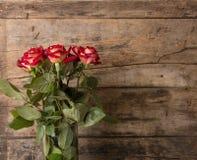 Bündel rote Rosen im Vase auf hölzernem Hintergrund Lizenzfreie Stockbilder