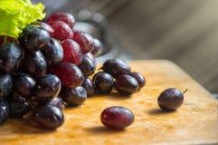 Bündel rote, schwarze, purpurrote Trauben legen auf Holztische mit lig Stockbild