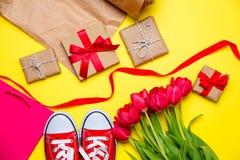 Bündel rote Tulpen, rote Gummiüberschuhe, kühle Einkaufstasche, Sachen für Lizenzfreies Stockbild