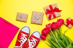 Bündel rote Tulpen, rote Gummiüberschuhe, kühle Einkaufstasche und beautif Lizenzfreie Stockfotografie