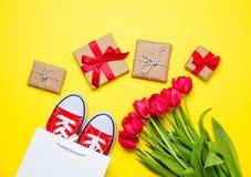 Bündel rote Tulpen, rote Gummiüberschuhe, kühle Einkaufstasche und beautif Stockfoto