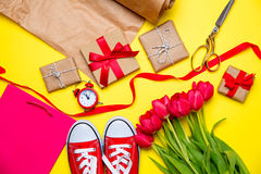 Bündel rote Tulpen, rote Gummiüberschuhe, kühle Einkaufstasche, Warnung cloc Stockfotografie